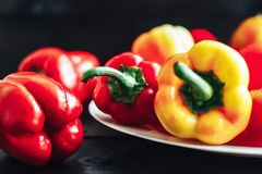 Red and yellow sweet bell peppers on wite plate close up Stock Photos