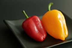 Red yellow sweet pepper. Two sweet peppers black background Stock Photo