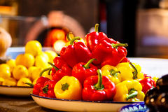 Red and yellow sweet peppers are in the background of the furnac Stock Photo