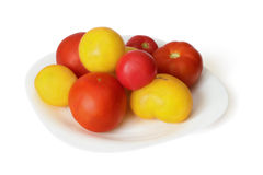 Red and yellow tomato on dish Stock Photos