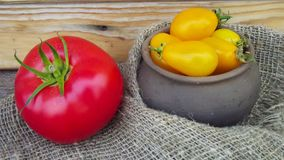 Red and yellow tomatoes. Red and yellow tomatoes in a basket and a pot stock photos