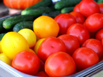 Red and yellow tomatoes and cucumbers. Stock Photo