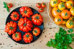 Red and yellow tomatoes on a plate on a wooden table.  Royalty Free Stock Photo