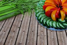 Red and yellow tomatoes sliced, lying on green cucumber plates. Fresh greens. Summer vegetarian food Royalty Free Stock Photos
