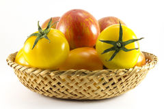 Red and yellow tomatoes in wicker oval shape Stock Photography