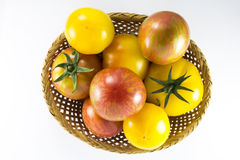Red and yellow tomatoes in wicker oval shape Stock Images