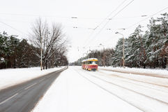 Red and yellow tram on a snow winter road Royalty Free Stock Photography