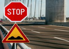 Red and yellow triangular warning road sign with STOP sign a warning of a bumpy road ahead. On a rod on bridge royalty free stock photos