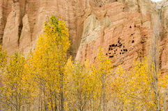 Red and yellow troglodyte dwellings in Dahkmar, Mustang. Dahkmar red cliffs, with its troglodyte caves and trees in autumn colors Stock Photo
