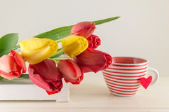 Red and yellow tulips on wooden table Royalty Free Stock Photography