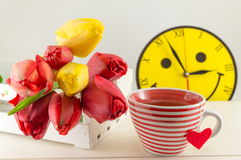 Red and yellow tulips on wooden table Royalty Free Stock Photos