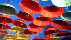 Red and yellow umbrella heap on blue sky, enternainment details, stock video