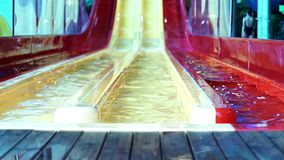 Red and yellow water slides in summer aqua park. Attractions in the aqua park. Multicolored water slides and pool in the aqua park stock video
