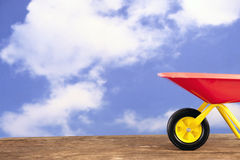 Red and yellow wheelbarrow agains a blue sky Stock Photo
