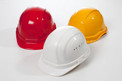 Red yellow white hardhats on white background Stock Photography