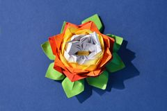 Origami paper flower. Red, yellow and white origami paper water lily flower on blue background stock image