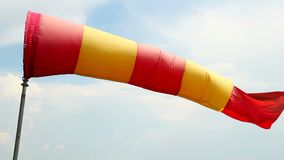 Red and yellow wind sock close-up shot, daytime cloudy weather stock video footage