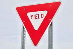 Red Yield Sign Against the Sky. Red and White Yield Sign Closeup with the sky as background royalty free stock images
