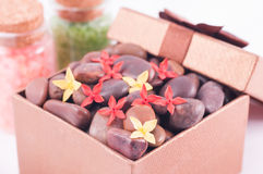Red zen stones in a bronze gift box with red and yellow flowers Royalty Free Stock Images