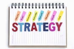 Redacta estrategia en el cuaderno sobre el fondo blanco imagenes de archivo