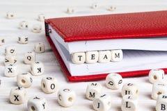 Redacte al equipo escrito en bloques de madera en cuaderno rojo en la madera blanca Imagen de archivo libre de regalías