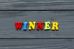 Redacte al ganador del ` que el ` de letras magnéticas plásticas coloreadas en gris backgroundwooden foto de archivo