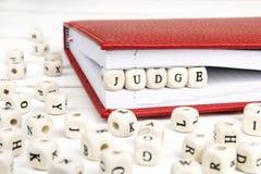 Redacte al juez escrito en bloques de madera en cuaderno rojo en blanco cortejan fotografía de archivo libre de regalías