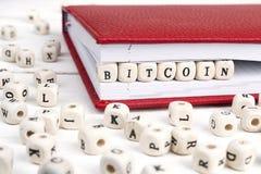 Redacte Bitcoin escrito en bloques de madera en cuaderno rojo en w blanco Foto de archivo libre de regalías