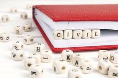 Redacte civil escrito en bloques de madera en cuaderno en de madera blanco Fotos de archivo
