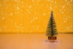 Redacte diciembre encendido wodden la tabla con el árbol de navidad y el fondo amarillo Fotos de archivo libres de regalías