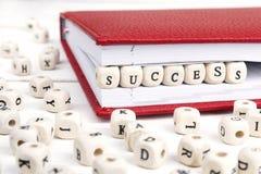 Redacte el éxito escrito en bloques de madera en cuaderno rojo en w blanco Fotografía de archivo