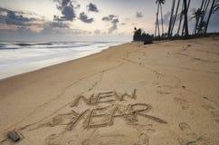 redacte el AÑO NUEVO escrito en la arena de la playa sobre fondo de la puesta del sol, Foto de archivo libre de regalías