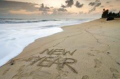 redacte el AÑO NUEVO escrito en la arena de la playa sobre fondo de la puesta del sol, Fotos de archivo