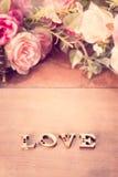 Redacte el amor con la flor color de rosa en la tabla de madera, imágenes de archivo libres de regalías