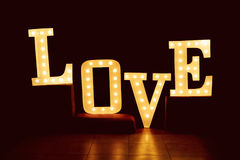 Redacte el amor de letras grandes con las bombillas que brillan intensamente en los vagos oscuros Fotografía de archivo libre de regalías