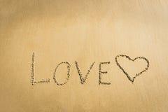 Redacte el amor escrito en el concepto romántico dibujado corazón del símbolo del mensaje de la arena Imagenes de archivo