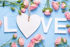 Redacte el amor hecho de las letras de madera blancas, del corazón blanco y de r rosado Foto de archivo