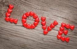 Redacte el AMOR presentado del caramelo en forma del corazón en fondo de madera Imagen de archivo