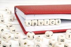 Redacte el consejo escrito en bloques de madera en cuaderno rojo en el wo blanco fotografía de archivo