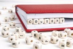 Redacte el contenido escrito en bloques de madera en cuaderno rojo en w blanco Imágenes de archivo libres de regalías