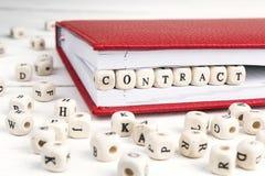 Redacte el contrato escrito en bloques de madera en cuaderno rojo en blanco Fotos de archivo