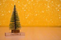 Redacte el ` de enero del ` encendido wodden la tabla con el árbol de navidad y el fondo amarillo Fotos de archivo