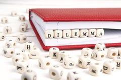 Redacte el dilema escrito en bloques de madera en cuaderno rojo en w blanco Imagen de archivo