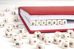 Redacte el divorcio escrito en bloques de madera en cuaderno rojo en w blanco Fotos de archivo