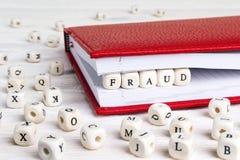 Redacte el fraude escrito en bloques de madera en cuaderno rojo en blanco cortejan Fotografía de archivo