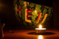Redacte el infierno tallado en una sandía, velas ardientes y libros viejos en fondo oscuro Fotografía de archivo
