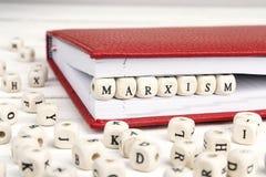 Redacte el marxismo escrito en bloques de madera en cuaderno rojo en w blanco Foto de archivo libre de regalías