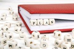 Redacte el plan escrito en bloques de madera en cuaderno rojo en la madera blanca Imagenes de archivo