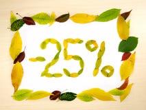 Redacte el 25 por ciento hecho de las hojas de otoño dentro del marco de las hojas de otoño en el fondo de madera Venta del veint Imagen de archivo