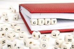Redacte el regalo escrito en bloques de madera en cuaderno rojo en la madera blanca Fotos de archivo libres de regalías
